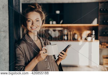 Lovely Happy Young Woman Having Her Morning Coffee While Checking New Emails And Notifications On Sm