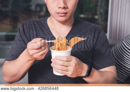 A Man Holding A Plastic Fork With Cooked Instant Noodles. Instant Noodle Is Convenient And Delicious