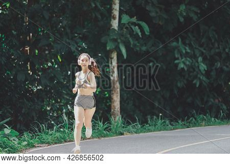 Young Woman Runner Listening Music On Headphones While Running On Road In The Morning.