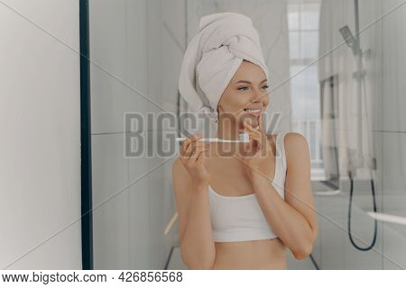 Oral Hygiene Concept. Healthy Beautiful Woman With White Bath Towel On Head Brushing Teeth During Mo