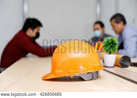 Close Up Image Of A Helmet On The Desk With Architects Wearing Protective Masks Working Together In