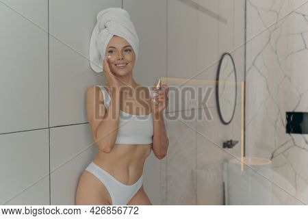 Young Beautiful Woman Using Face Moisturizing Serum After Taking Shower In Bathroom At Home, Looking
