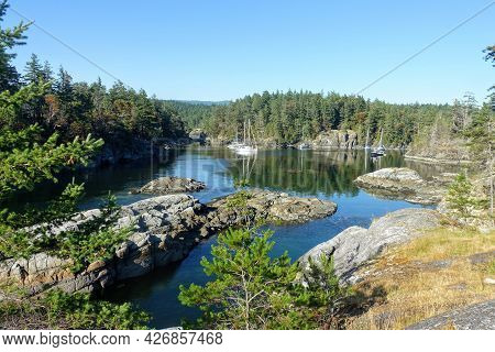 A View Of A Beautiful Remote Rocky Cove Surrounded By Trees And Pristine Blue Water, With Boats Anch
