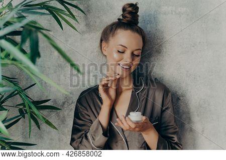 Beautiful Europian Brunette Woman At Home In Silk Brown Pajama Doing Beauty Procedures, Applying Moi