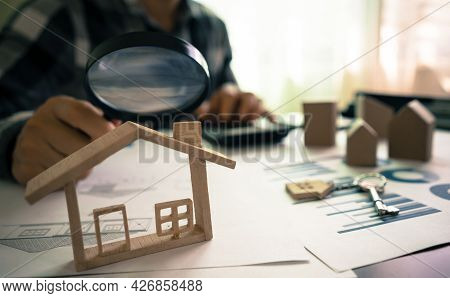 Real Estate Or House Appraisal Using Magnifying Glass Over The Model Of A Wooden House. Concept Of H