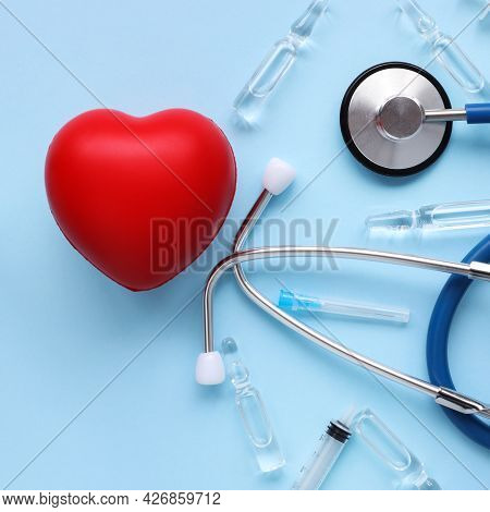 Stethoscope And Red Hearts On Blue Background Health Care Concept. Transparent Ampoules. Amelioratio