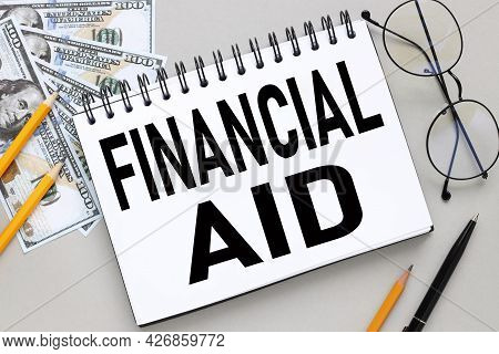 Financial Aid. Notepad On A Gray Background Near Bills And Pencils