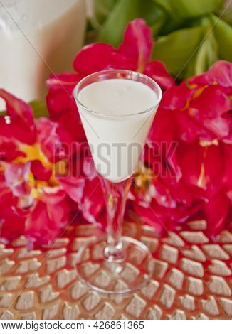 Closeup Of A Coconut Liqueur Glass With Some Beautiful Flowers In The Background