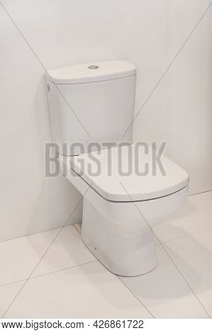 Closed Seat At Toilet Block In Clean White Bathroom
