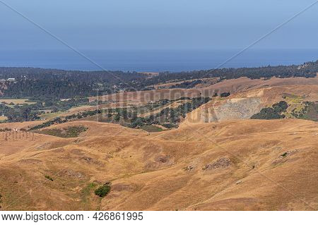 Cambria, Ca, Usa - June 8, 2021: Landscape With Open Pit Quarry Behind Brown Dry Ranching Land On Hi