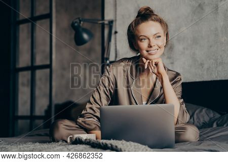 Portrait Of Beautiful Thoughtfully Smiling Businesswoman In Satin Pajama Working Remotely From Home