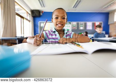 Portrait of african american girl smiling while sitting on her desk at elementary school. school and education concept