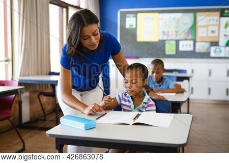 African american female teacher teaching african american girl in the class at elementary school. school and education concept