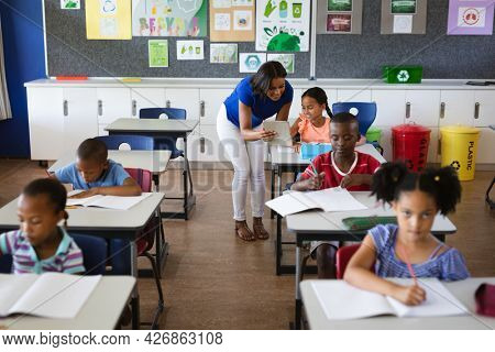 African american female teacher with digital tablet teaching a girl at elementary school. school and education concept