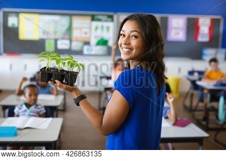 African american female teacher smiling while holding plant seedlings in class at elementary school. school and education concept