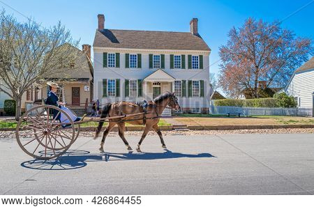 Williamsburg, Virginia, USA: 31st March 2021; Woman riding on a horse and buggy in colonial Williamsburg