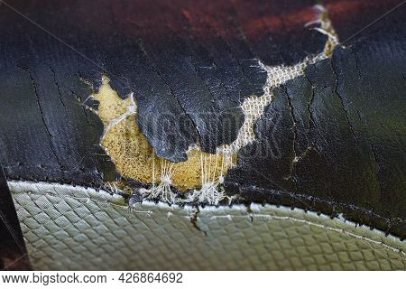 Part Of Old Upholstery Made Of Black Gray Torn Leather With A Hole