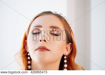 Close-up Portrait Of A Red-haired Caucasian Woman With Closed Eyes With Pearl Makeup, A Pearl Mother