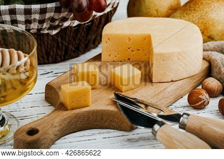 Cheese Dish With Organic Cheeses, Fruits, Nuts On A Wooden Background. Delicious Cheese Snack