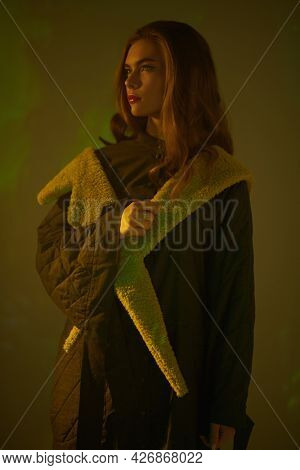 A thoughtful beautiful model girl in a stylish coat poses in yellow and green light in dark at the studio. Fashion collection. Haute couture clothing.