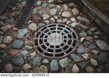 An Old Metal Sewer Manhole Among The Cobblestones. Valdai. Novgorod Region. Russia. May 2021