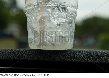 A Cup Of Ice Melting On The Dash Of A Car With Bokeh Background