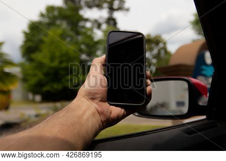 Person Holding A Cellphone Out Of A Car Window With Bokeh Background Focus On Phone