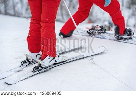 Legs Of Skier And Snowboarder In Bright Red Tracksuits Standing On Ski Slope. Selective Focus. Winte
