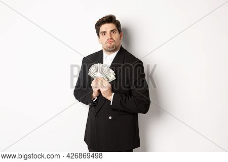 Image Of Greedy Guy In Black Suit, Holding Money And Unwilling To Share, Standing Over White Backgro