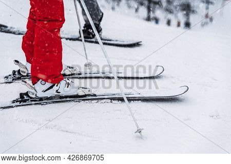 Close-up Of Skier Legs In Boots And Skis. Ski Slope, Blurred Selective Focus. Winter Leisure, Sport