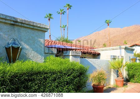 Manicured Plants And Palm Trees On An Outdoor Patio Besides A Historic Spanish Colonial Style Buildi
