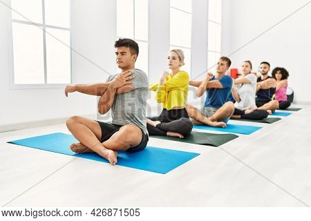 Group of young people concentrated stretching at sport center.