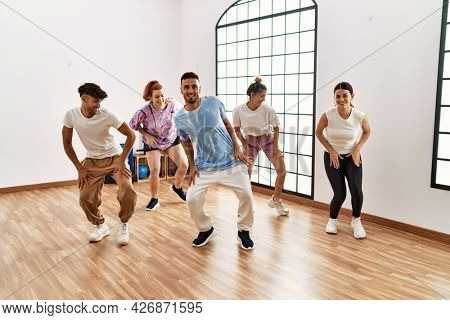 Group of young dancer smiling happy dancing choreography at dance academy.