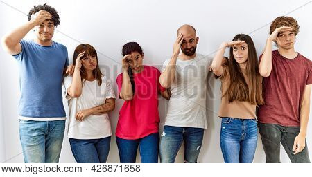Group of young friends standing together over isolated background worried and stressed about a problem with hand on forehead, nervous and anxious for crisis