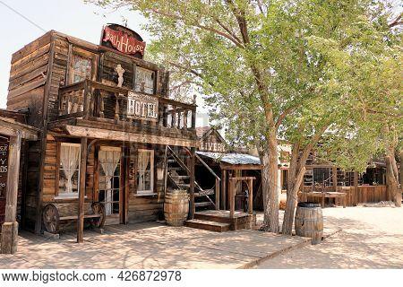 July 14, 2021 In Pioneertown, Ca:  Vintage Rustic Buildings Besides A Wooden Boardwalk And Cottonwoo