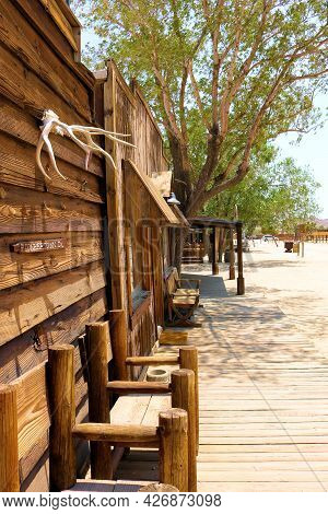 July 14, 2021 In Pioneertown, Ca:  Rustic Chairs On A Wooden Boardwalk Besides Historical Buildings