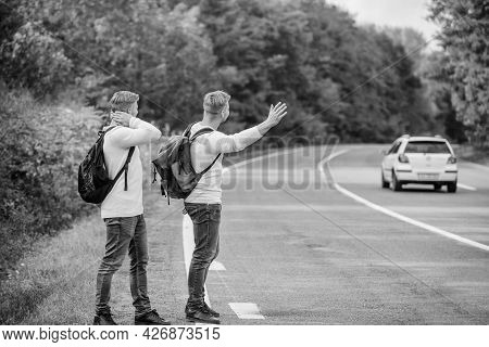 Meet New People. Looking For Transport. Twins Walking Along Road. Stop Car With Thumb Up Gesture. Hi