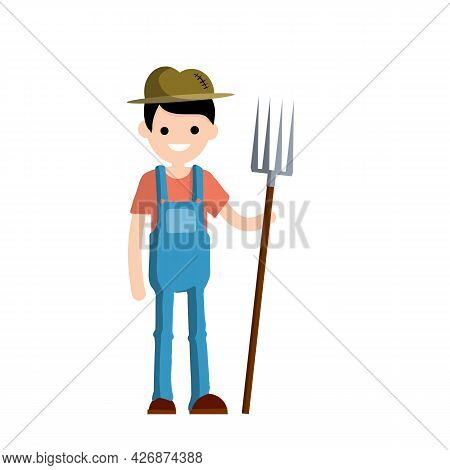 Man Farmer In Overalls With Fork In Hands. Rural Type Of Work. Production Of Natural Food In The Vil