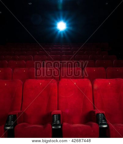 Empty comfortable red seats with numbers in cinema poster