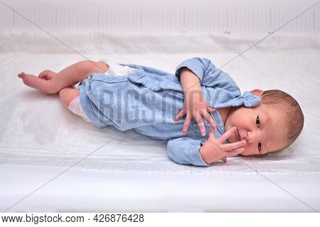 A Newborn Baby In Blue Clothes On A Changing Table With A Moro Reflex