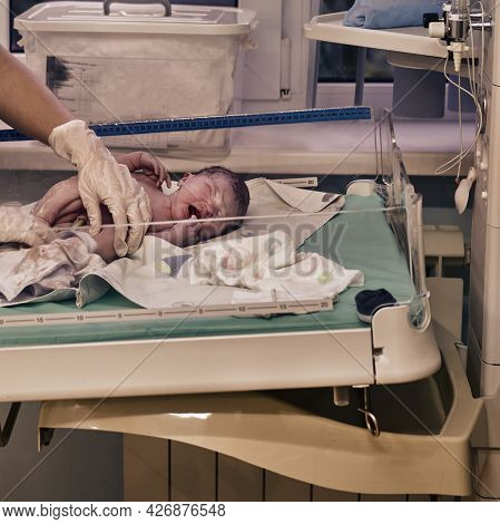 A Newborn Baby Is Examined By A Doctor After Childbirth. Checking The Baby After Birth On The Apgar