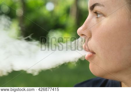 Vape Smokes. The Girl Lets Out Smoke From Her Mouth And Nose In Close-up. Portrait Of A Smoking Girl