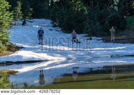 Washington, Usa - July 6, 2021: Three Hikers Carefully Go Off Trail To Cross A Snow Field, In Mt Rai