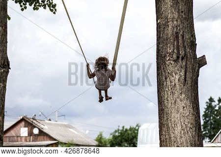 Girl Riding A Swing High Among The Trees