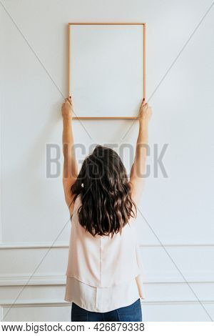 Curator hanging blank frame on a wall