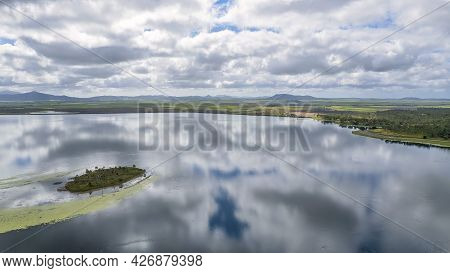 Clouds Reflected In The Mirror Like Surface Of The Dam Water Across A Tiny Island Towards The Shorel
