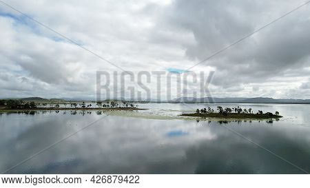 A Stormy Cloudy Sky Is Reflected In The Calm Water Across Kinchant Dam, Queensland, Australia.