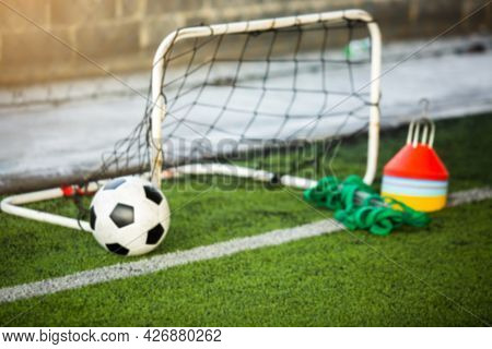 Blurry Soccer Ball With Mini Goal And Soccer Training Equipment On Green Artificial Turf.
