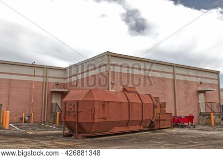 A Large Trash And Waste Compactor Behind A Building And Abandoned Shopping Carts