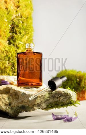 Amber Cosmetic Bottle With Dropper On A Natural Stone Podium. Natural Stone, Bricks With Moss In A B